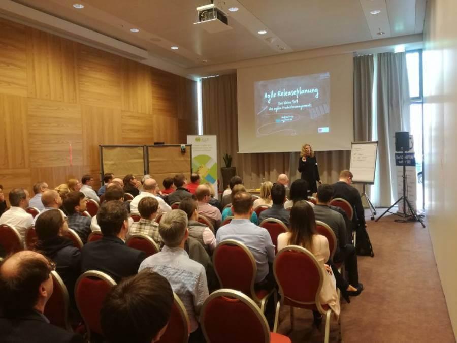 Agile Releaseplanung - Andrea Grass vor vollen Stuhlreihen und großem Interesse der Teilnehmer